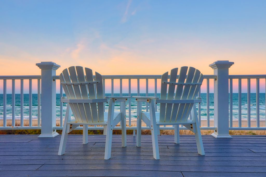 View of two chairs on the deck at sunset | Carolina Retreats